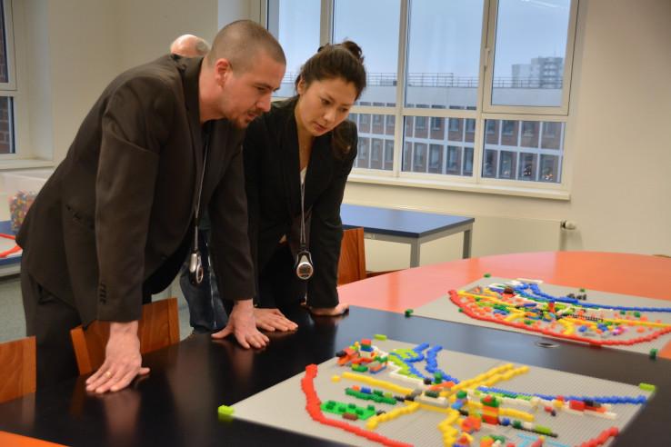 Workshop-Leiter Elisa Hofmann und Heiner Remmert betrachten die ersten Lego-Entwürfe; Foto: Vera Lisakowski