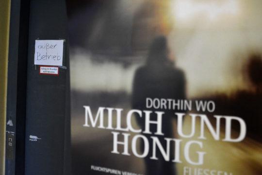 """Schild """"außer Betrieb"""" am Aufzug im Parkhaus, davor Plakat zu """"Dorthin wo Milch und Honig fließen"""". Foto: Vera Lisakowski"""