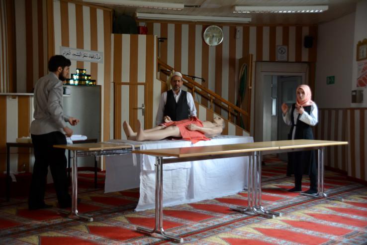 Drei Personen demonstrieren an einer Puppe die muslimische Leichenwaschung. Foto: Vera Lisakowski