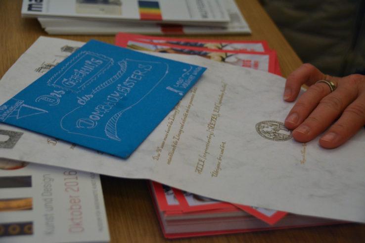 Blauer Briefumschlag auf einem Brief mit Siegel. Foto: Vera Lisakowski