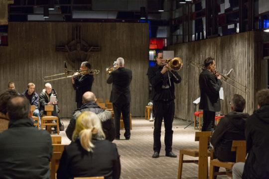 """Die vier Posaunisten des Posaunenquartetts """"Composers Slide Quartet"""" stehen mit den Rücken zueinander im Kirchenraum. Foto: Fabian Uhl / www.fabianuhl.de"""