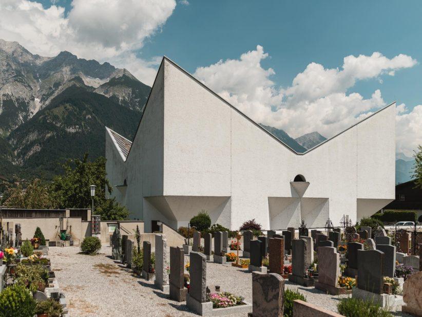 Helle Kirche mit steil gezacktem Dach vor Bergen. Foto: Gregor Zoyzoyla