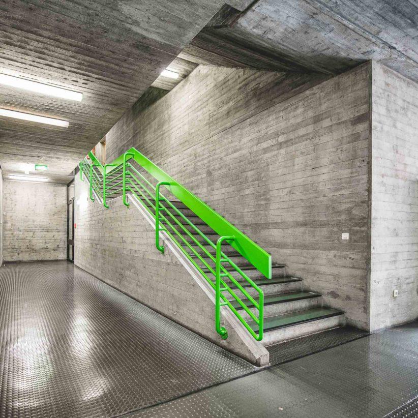 Leuchtend grünes Treppengeländer im Beton-Treppenhaus der Hochschule für Musik und Tanz Köln. Foto: Gregor Zoyzoyla